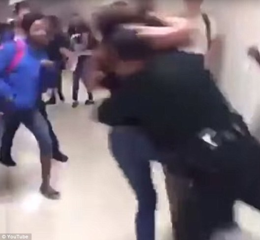 The guard is seen jumping into the frame and tackling the two girls to the ground, School Security Guard